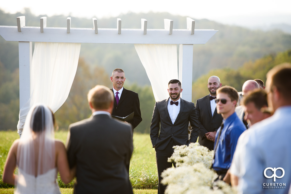 Groom sees his bride walking down the aisle.