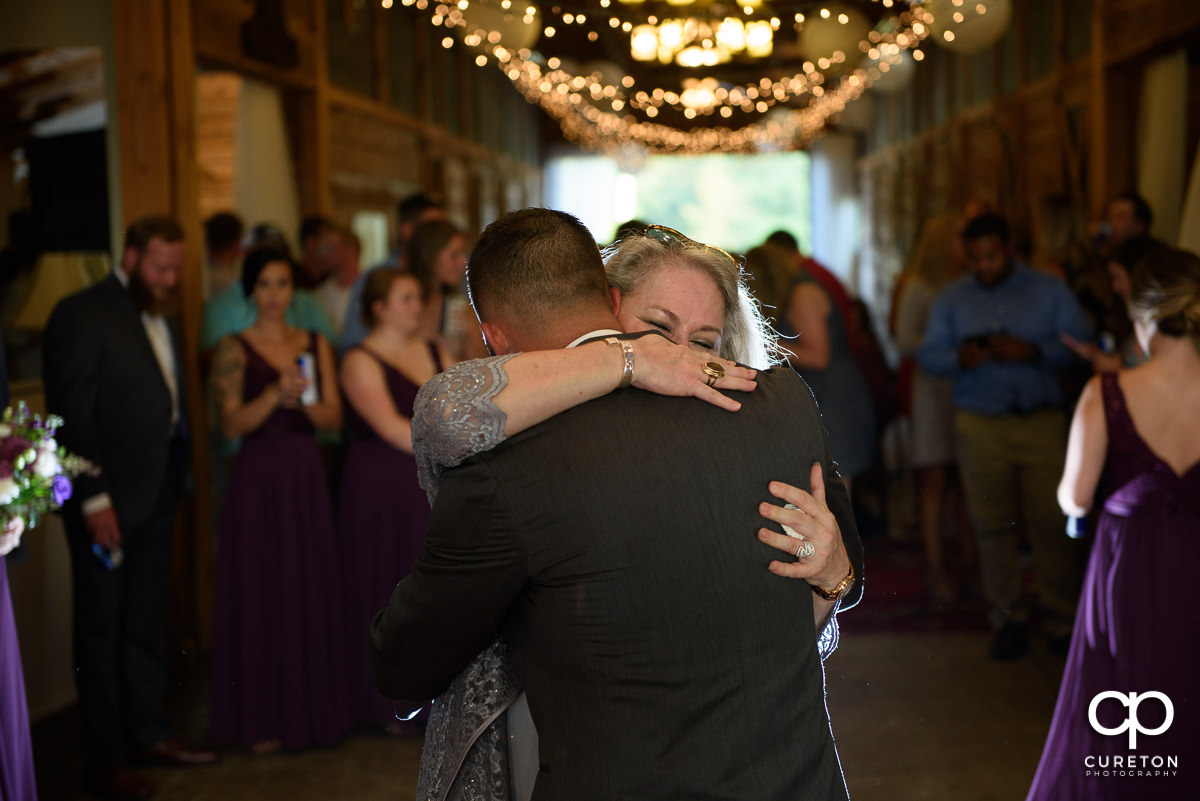 Mom hugging her son, the groom.