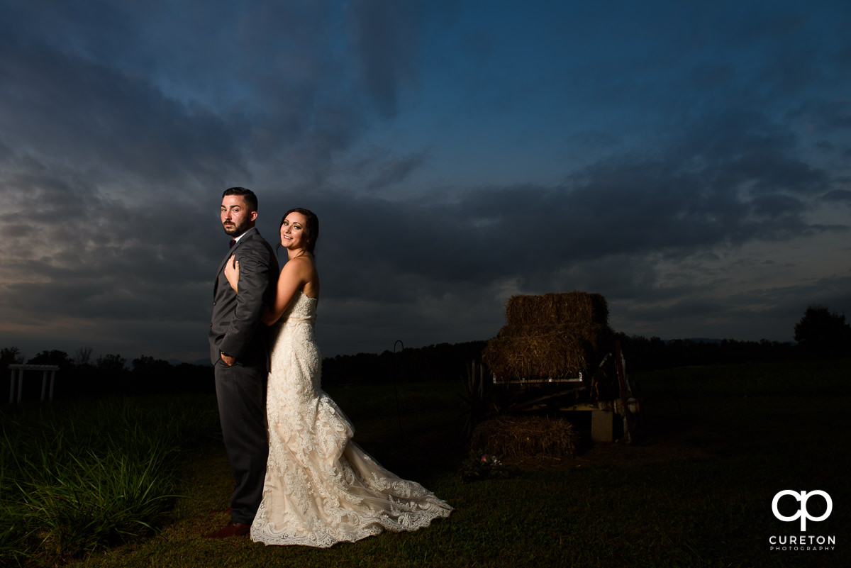 Bride holding her groom at sunset.