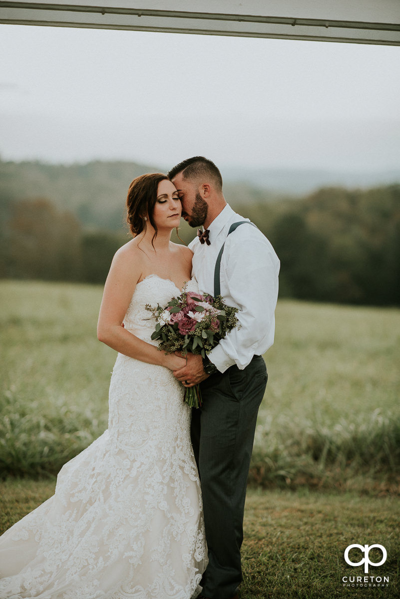 Bride and groom in the field at their rustic wedding minutes from Greenville,SC.