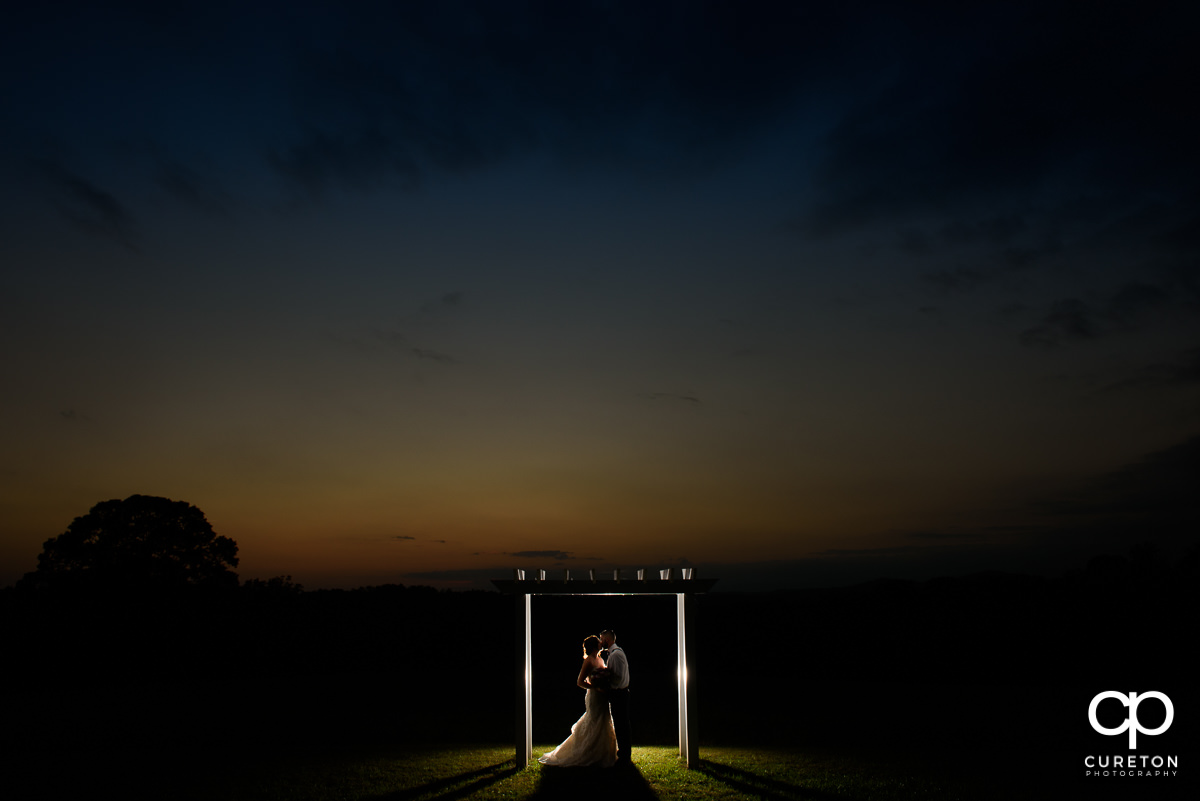 Backlit bride and groom at sunset at the alter.