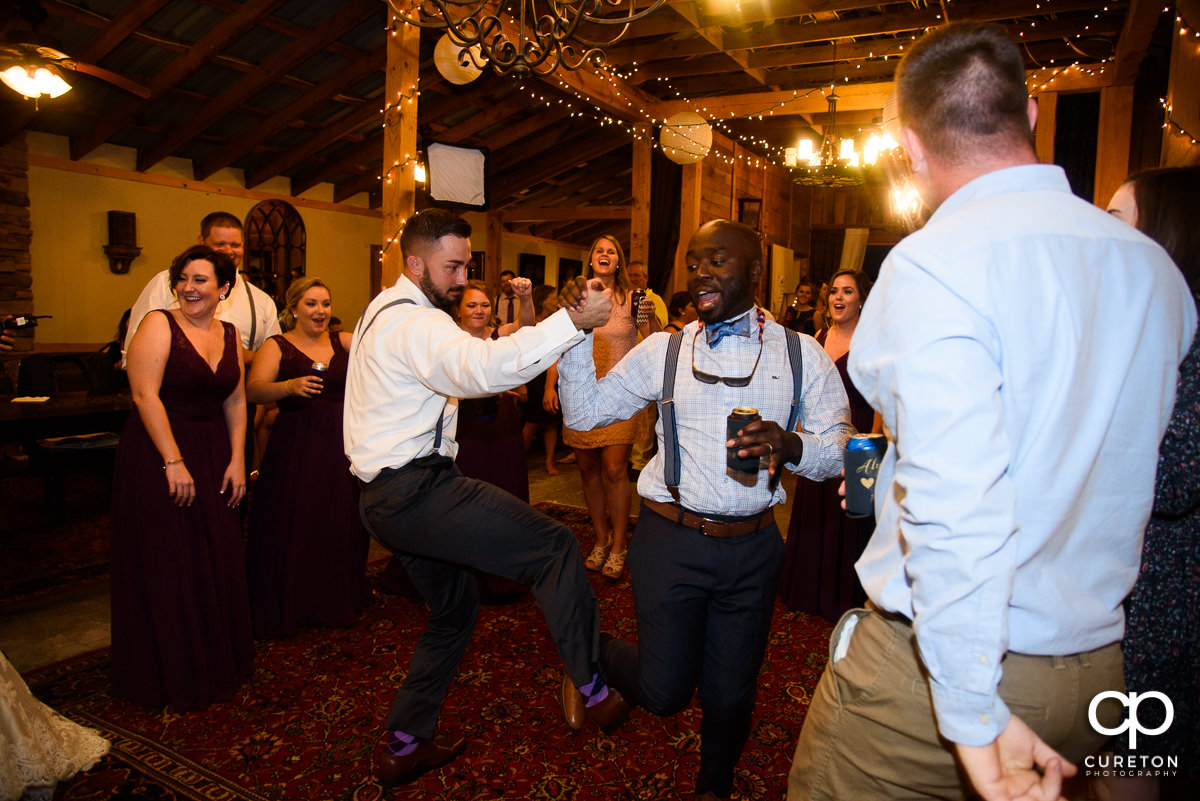 Groom dancing with a friend at the reception.