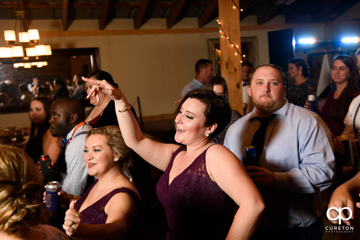 Bridesmaid dancing on a packed dance floor.