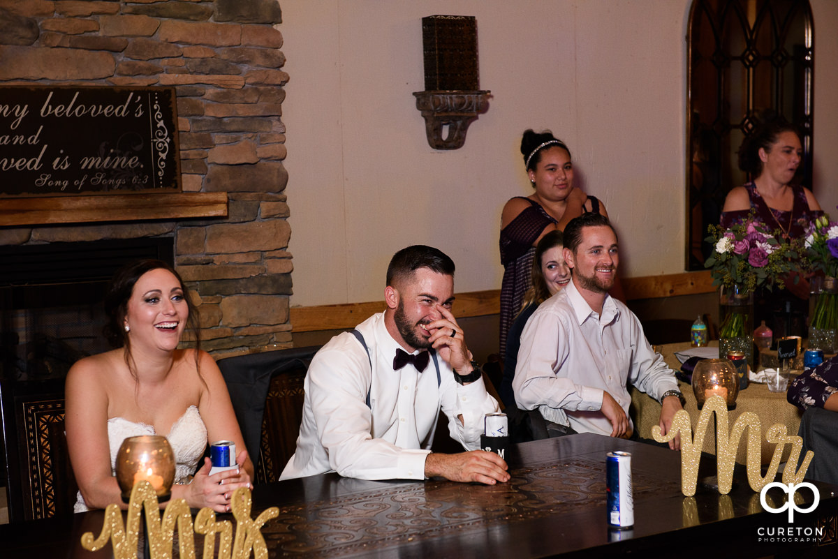 Bride and groom laughing during the toast.