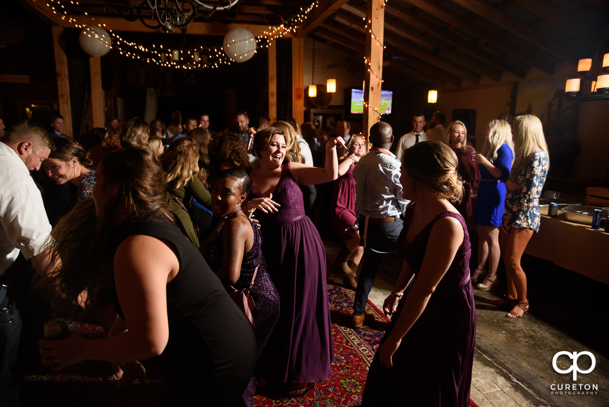 Wedding guests dancing at the reception on a packed dance floor.