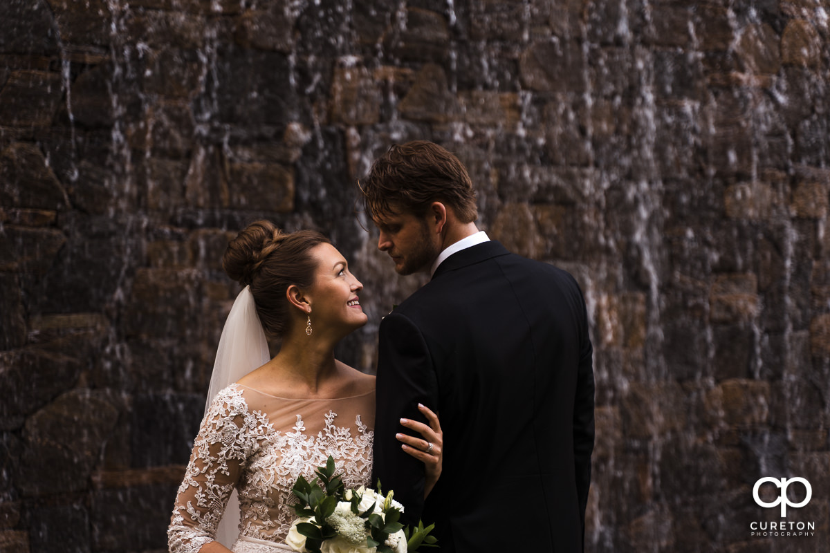 Bride and groom in front of a waterfall after their Loft at Soby's wedding in downtown Greenville,SC.