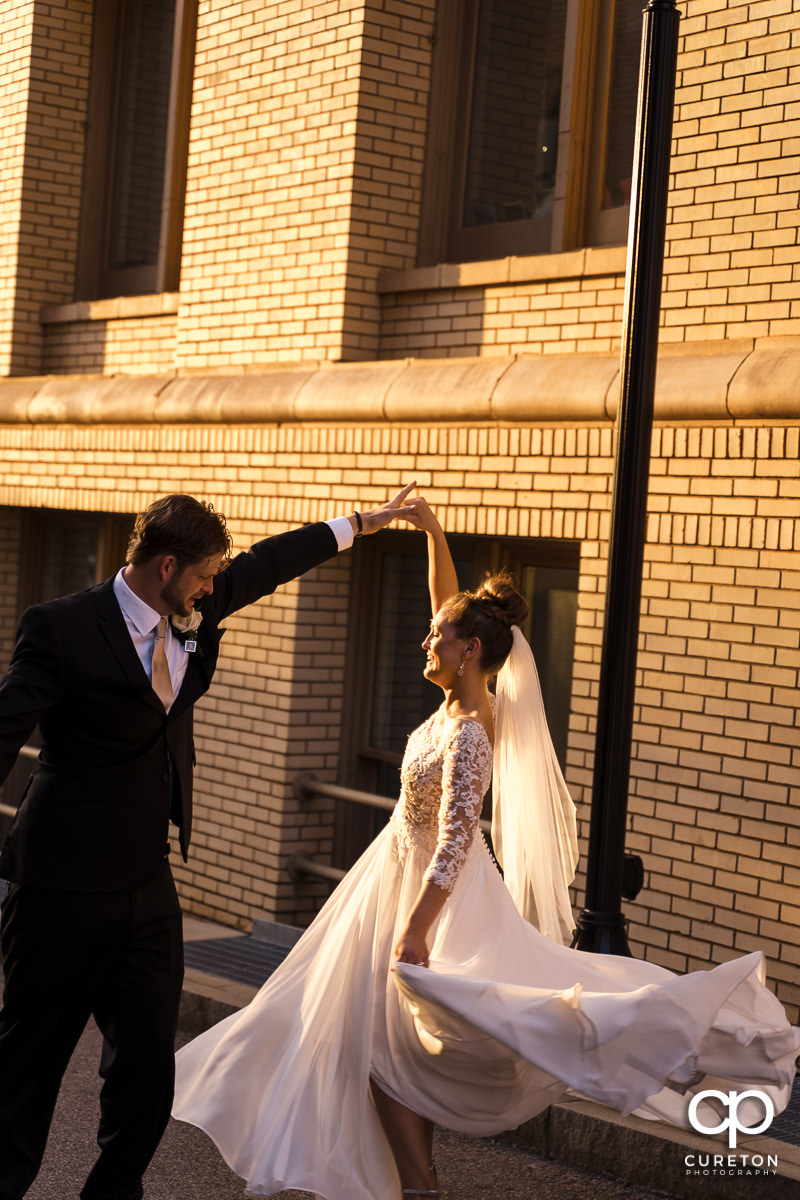 Bride and groom dancing in the sunlight on the streets on downtown Greenville SC after their wedding.