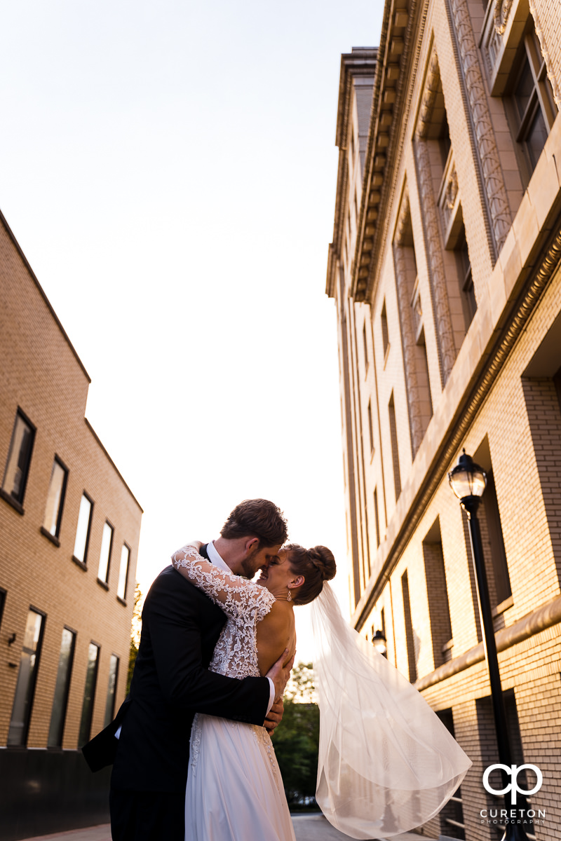 Groom dipping his bride while dancing in the streets of downtown Greenville,SC after their wedding.