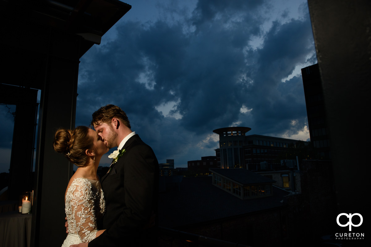 Groom kissing his bride at sunset on the rooftop at their Loft at Soby's wedding in downtown Greenville,SC.