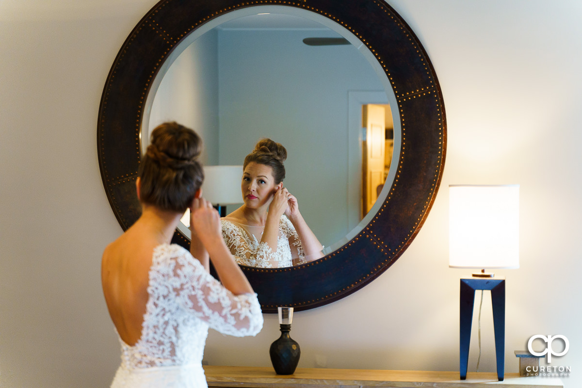 Bride putting her earrings on in the mirror.