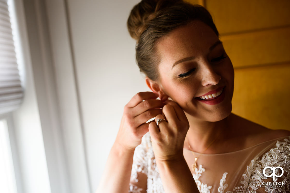 Bride smiling while putting her earrings on.