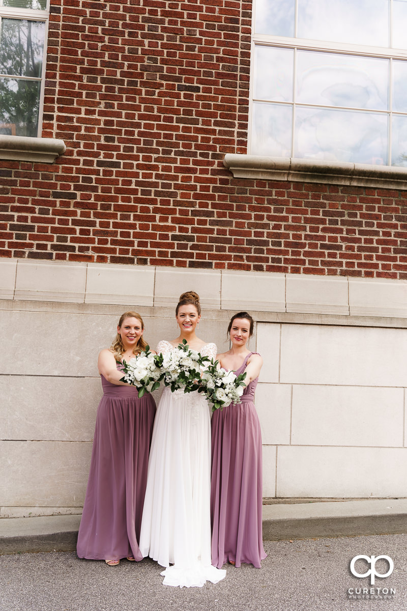 Bride and bridesmaids holding their flowers.