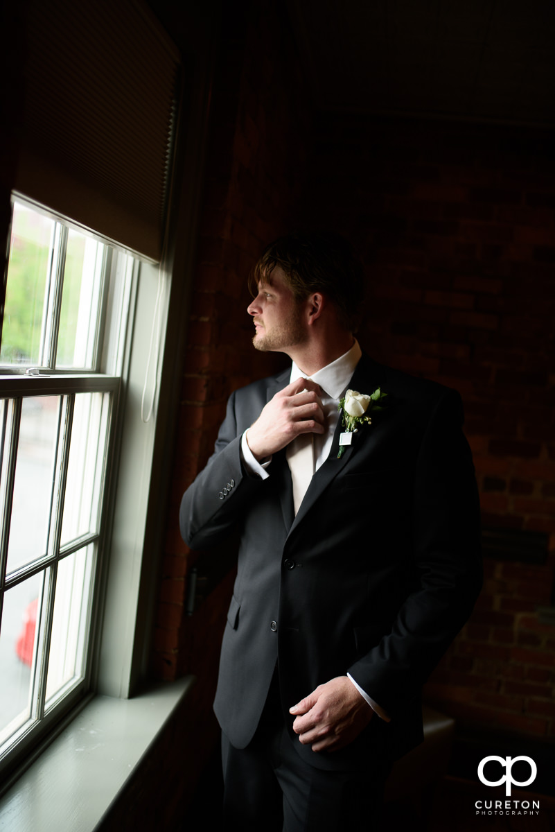 Groom fixing his tie in the window.