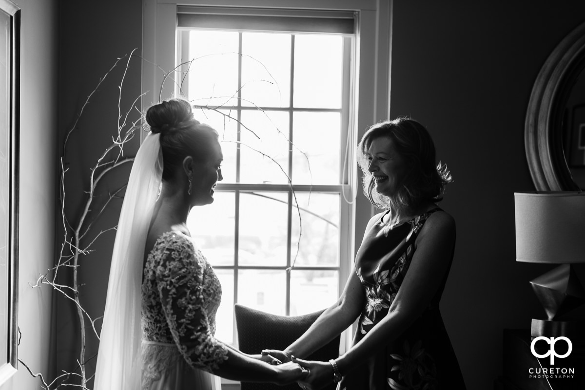 Bride's mother smiling at her as they share a moment before the ceremony at Soby's Loft.