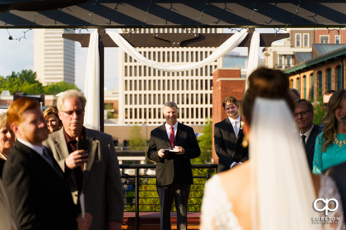 Groom seeing his bride for the first time as she walks down the aisle at their Loft at Soby's wedding in downtown Greenville,SC.