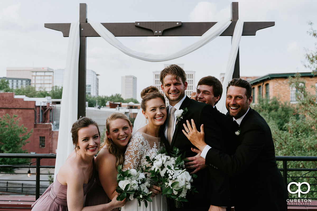 Bridal party hugging the bride and groom on a rooftop after the Soby's Loft wedding.