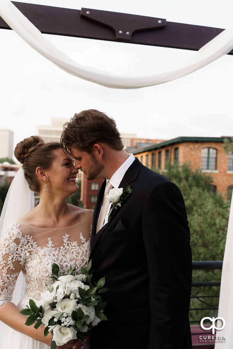 Bride and groom cuddling on teh rooftop after their Loft at Soby's wedding in downtown Greenville,SC.