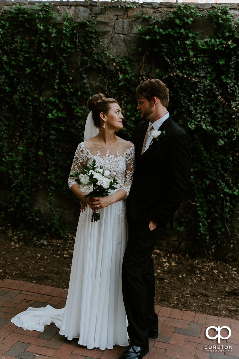 Bride and groom in front of a wall of ivy after their Loft at Soby's wedding in downtown Greenville,SC.