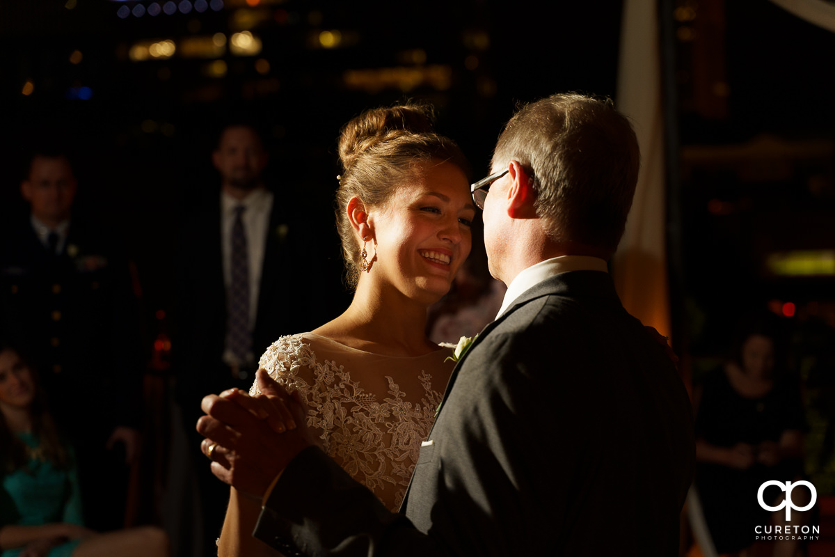 Bride smiling as she shares a dance with her father .