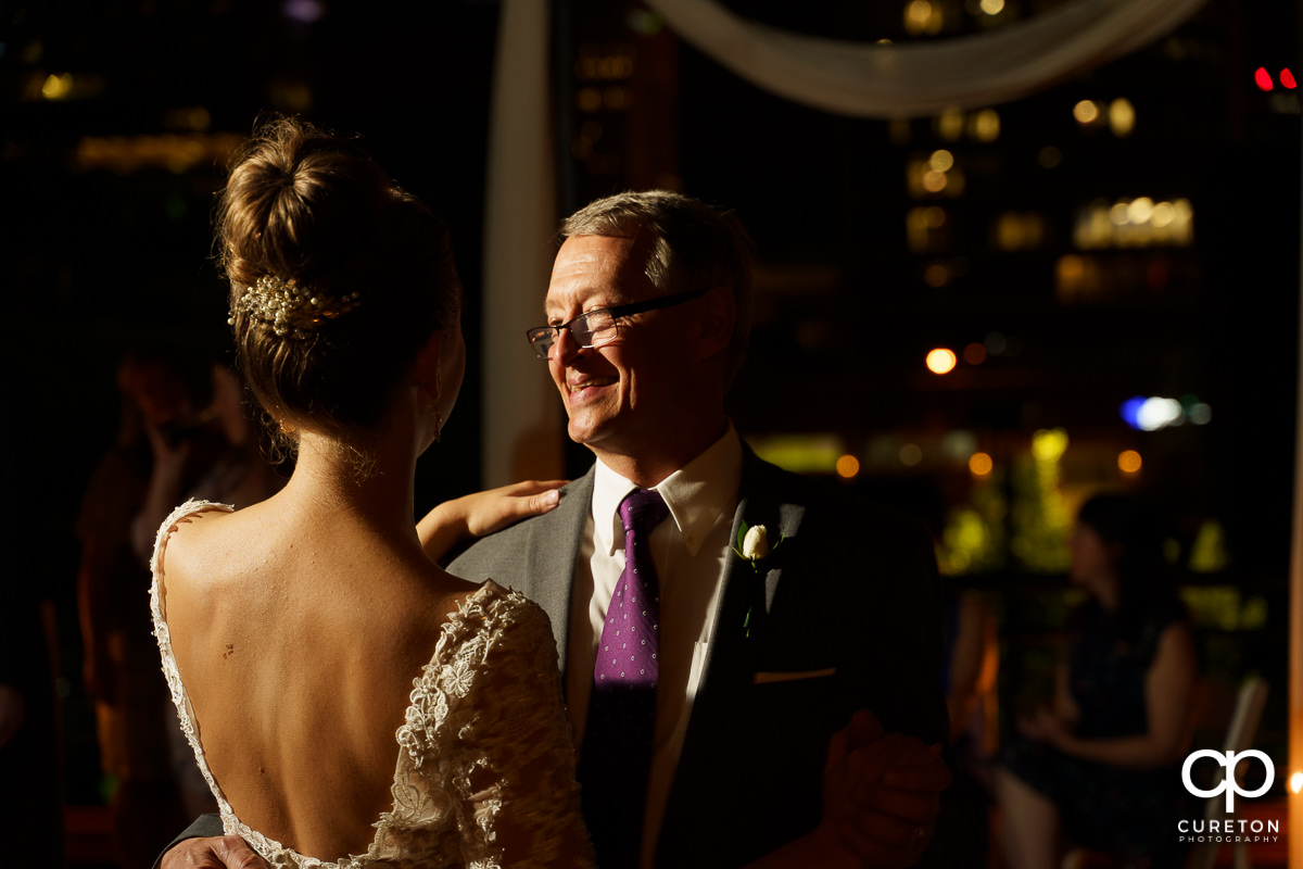 Bride's father smiling as he dances with his daughter at her wedding reception.