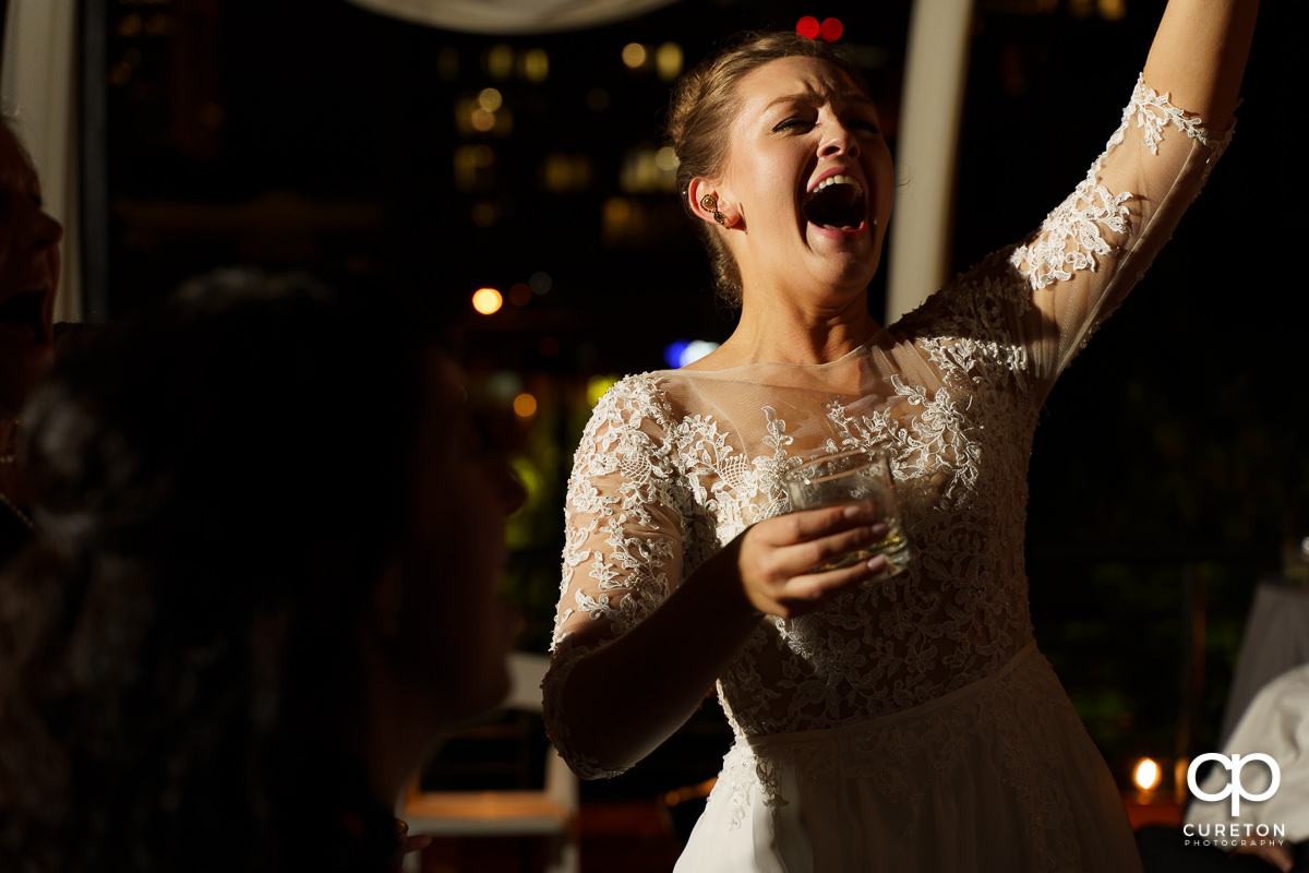 Bride screaming and dancing at the wedding reception on the rooftop at Soby's Loft in Greenville,SC.