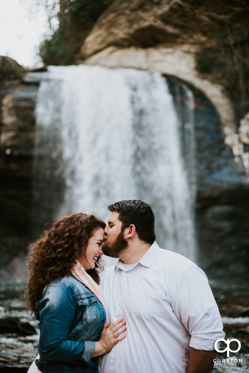 Groom kissing his bride on the forehead in a waterfall.