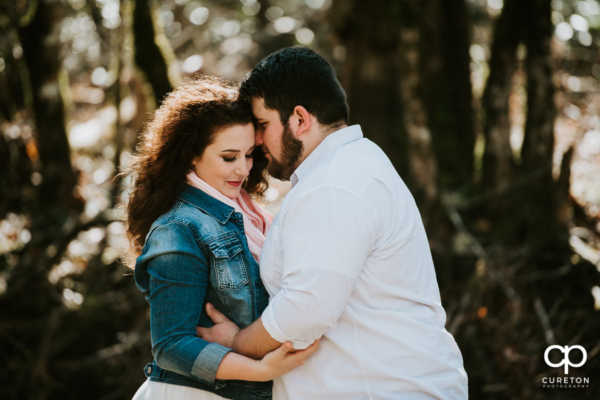 Future bride and groom hugging during an engagement session in Pisgah Forest.