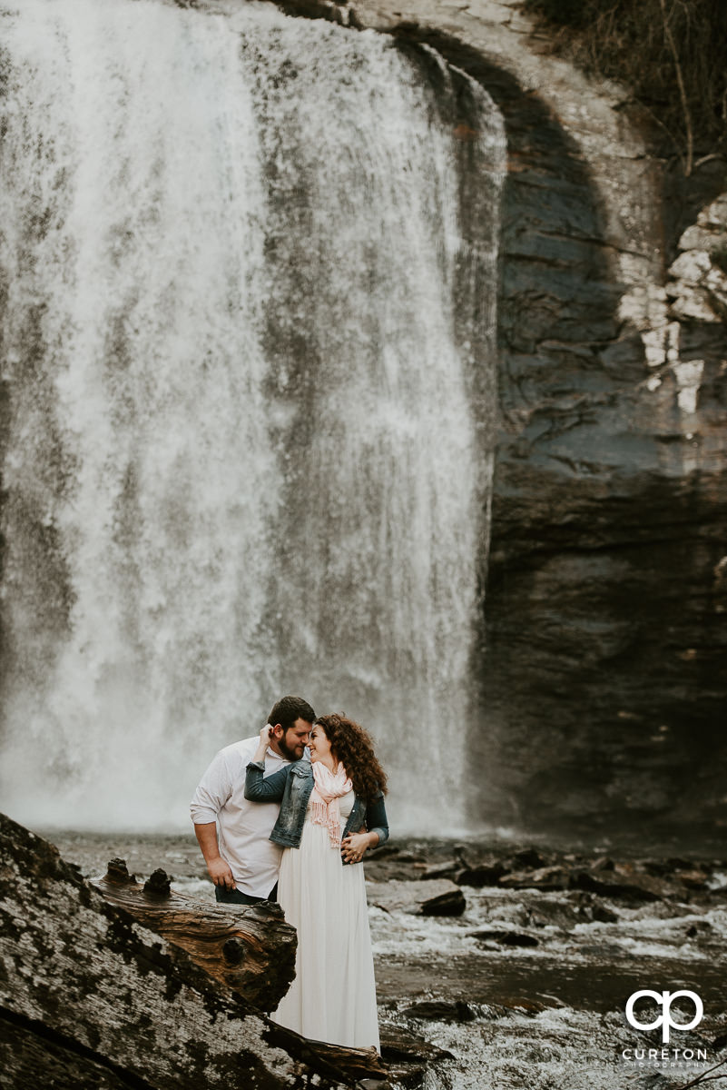 Bride and groom dancing in a waterfall during their Looking Glass Falls engagement session in the Pisgah Forest of North Carolina.