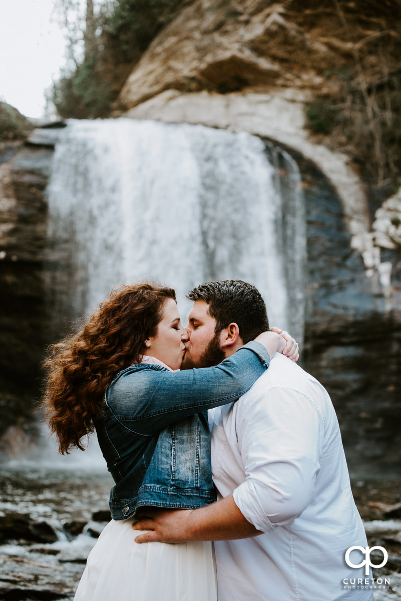 Engaged couple kissing in front of a waterfall.