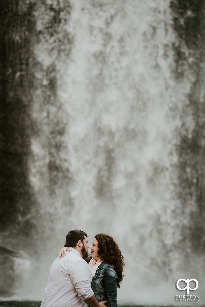 Bride and groom in front of Looking Glass Falls in Pisgah Forest.