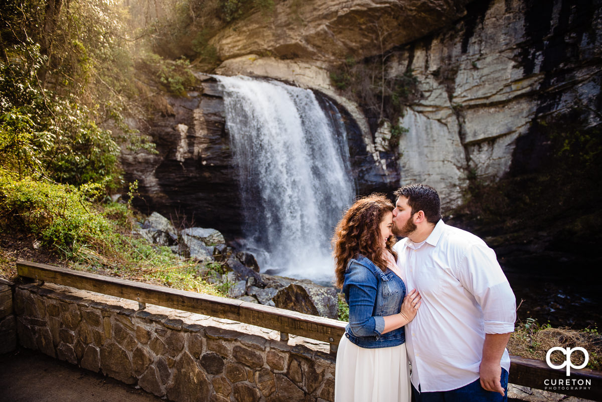 Groom kissing his bride on the forehead at the overlook of the waterfall.