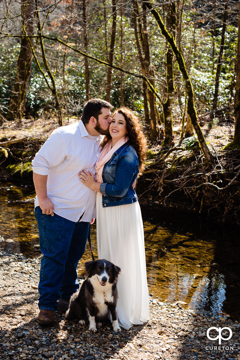 Bride and groom and their dog by the river in Pisgah Forest.