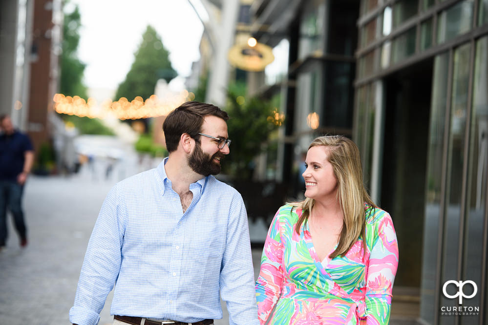 Engaged couple walking down the streets in downtown Greenville.
