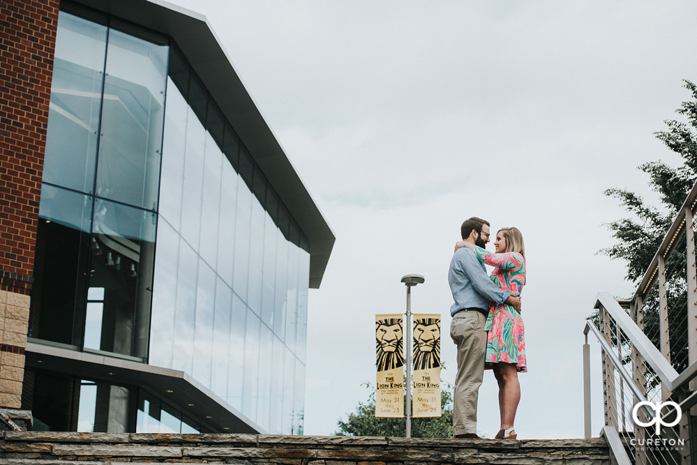 Bride and groom hugging during a Main Street Greenville SC engagement session.