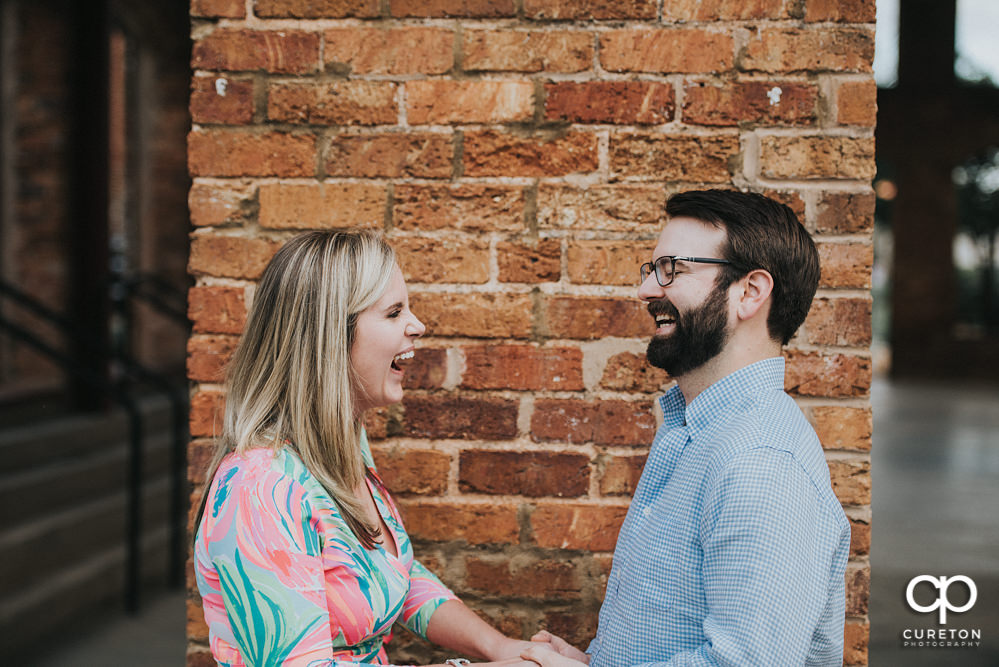 Bride and groom laughing during a Main Street Greenville SC engagement session.