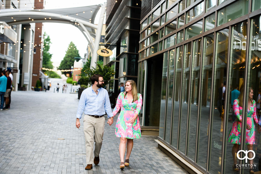Engaged couple strolling in downtown Greenville.