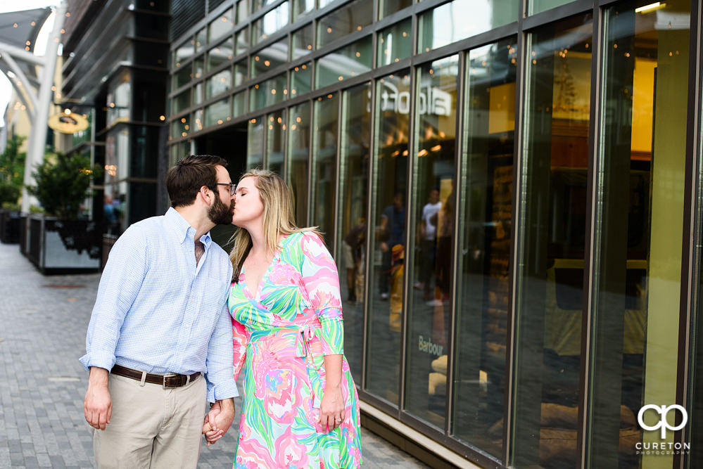 Engaged couple kissing during a Main Street Greenville SC engagement session.