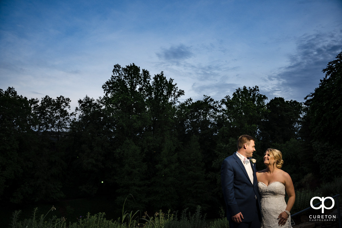 Bride and groom smiling at each other at sunset during their Mary's at Falls Cottage wedding in downtown Greenville,SC.