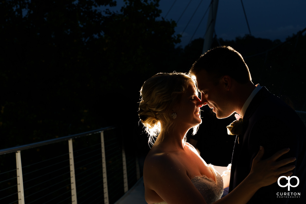 Bride and groom sharing a moment on the Liberty Bridge at night after their Mary's at Falls Cottage wedding in downtown Greenville,SC.