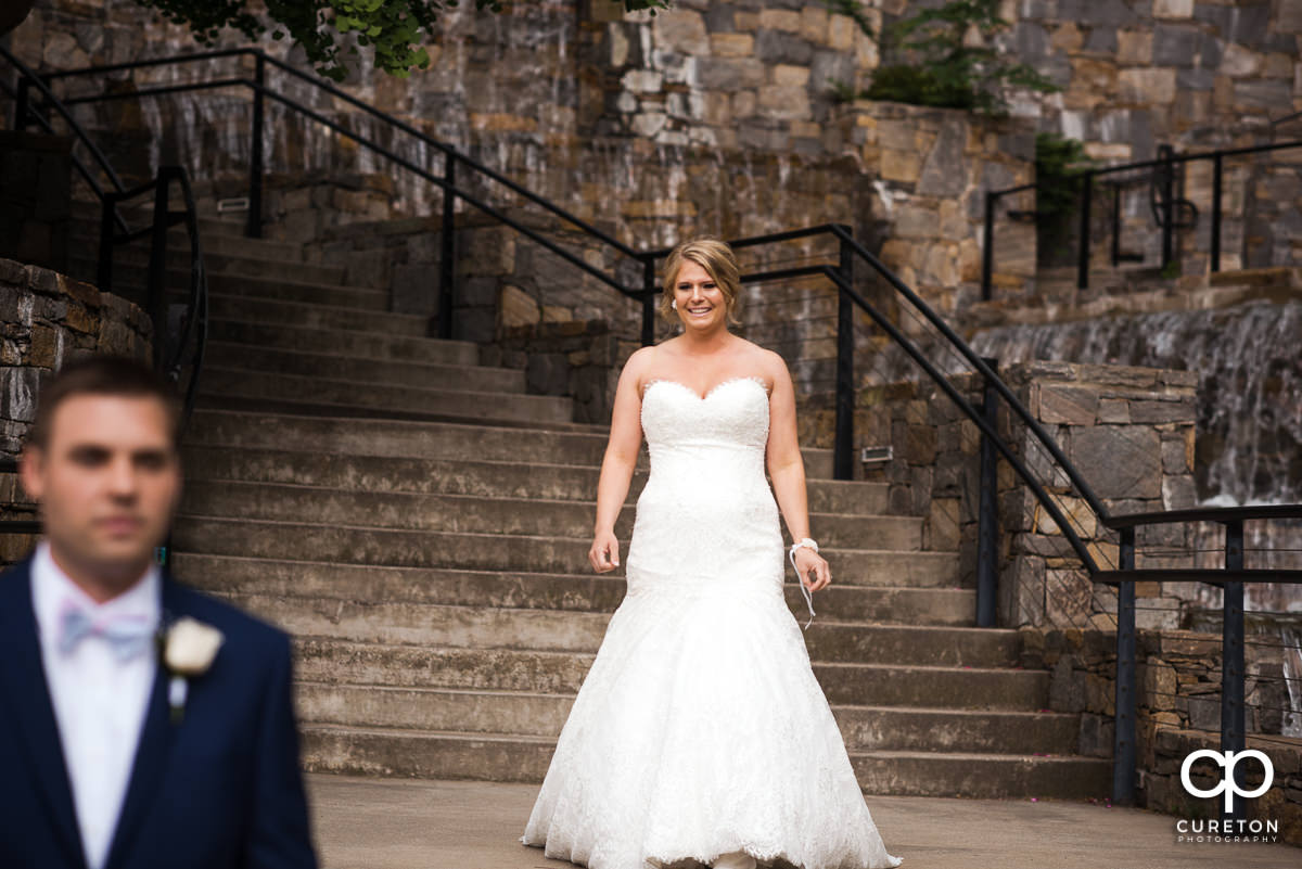 Bride preparing to sneak up on her groom at a pre-wedding first look in downtown Greenville.