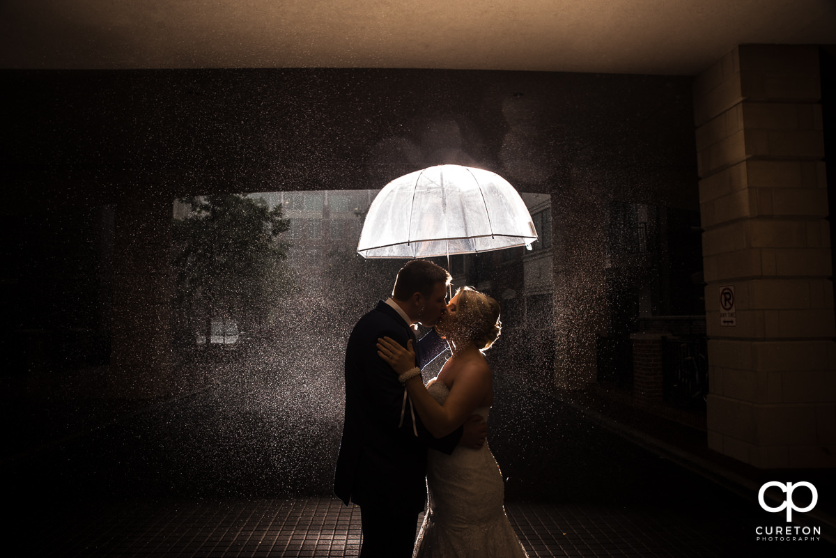 Bride and groom sharing a kiss in the rain before their Mary's at Falls Cottage wedding in downtown Greenville,SC.