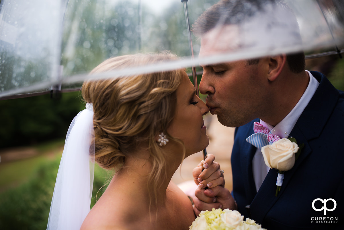 Groom kissing his bride on the noes underneath an umbrella in the rain before their Mary's at Falls Cottage wedding in downtown Greenville,SC.