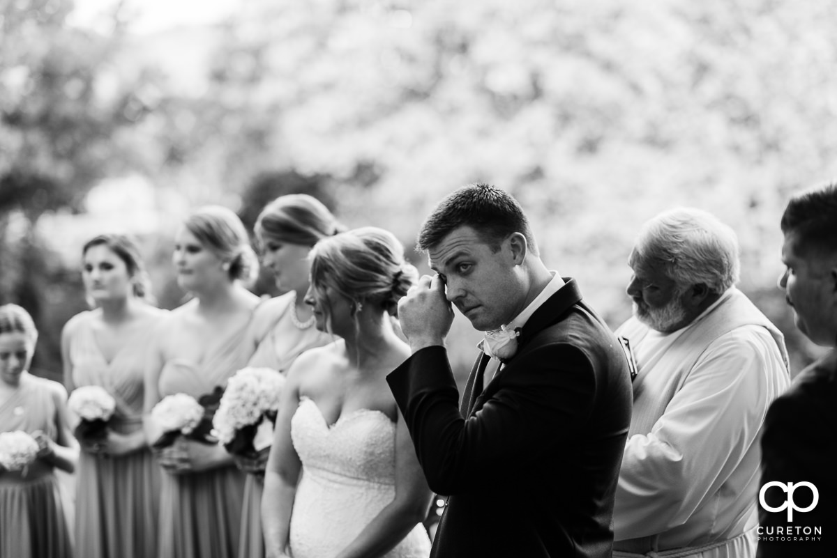 Groom wiping away tears at the wedding ceremony.