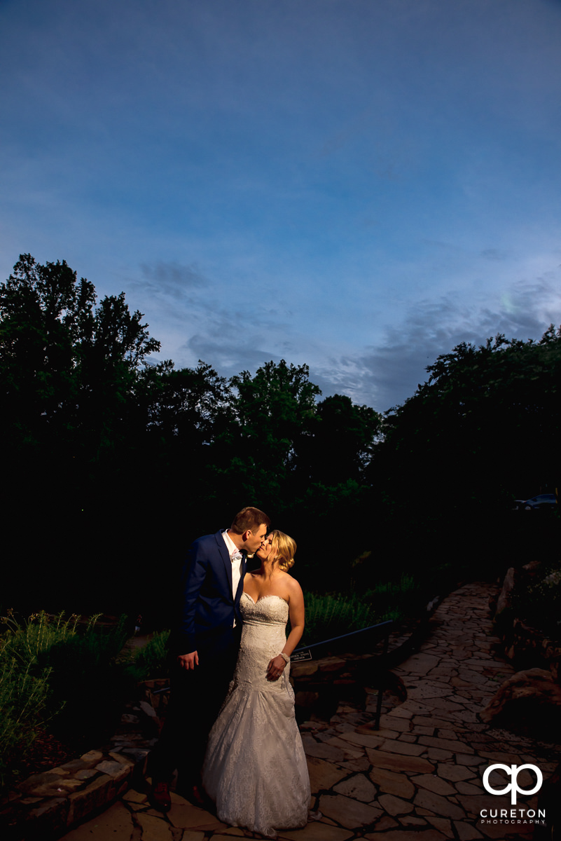 Bride and groom kissing in Falls Park at sunset.