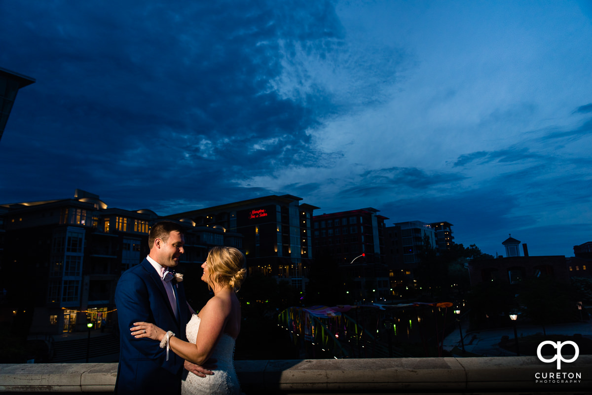 Bride and groom in front of a downtown Greenville,SC skyline at night.