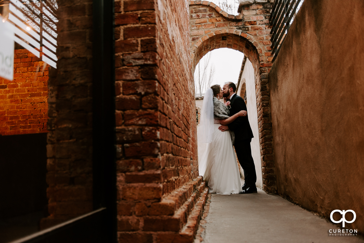 Groom kissing his bride outside of the Old Cigar Warehouse.