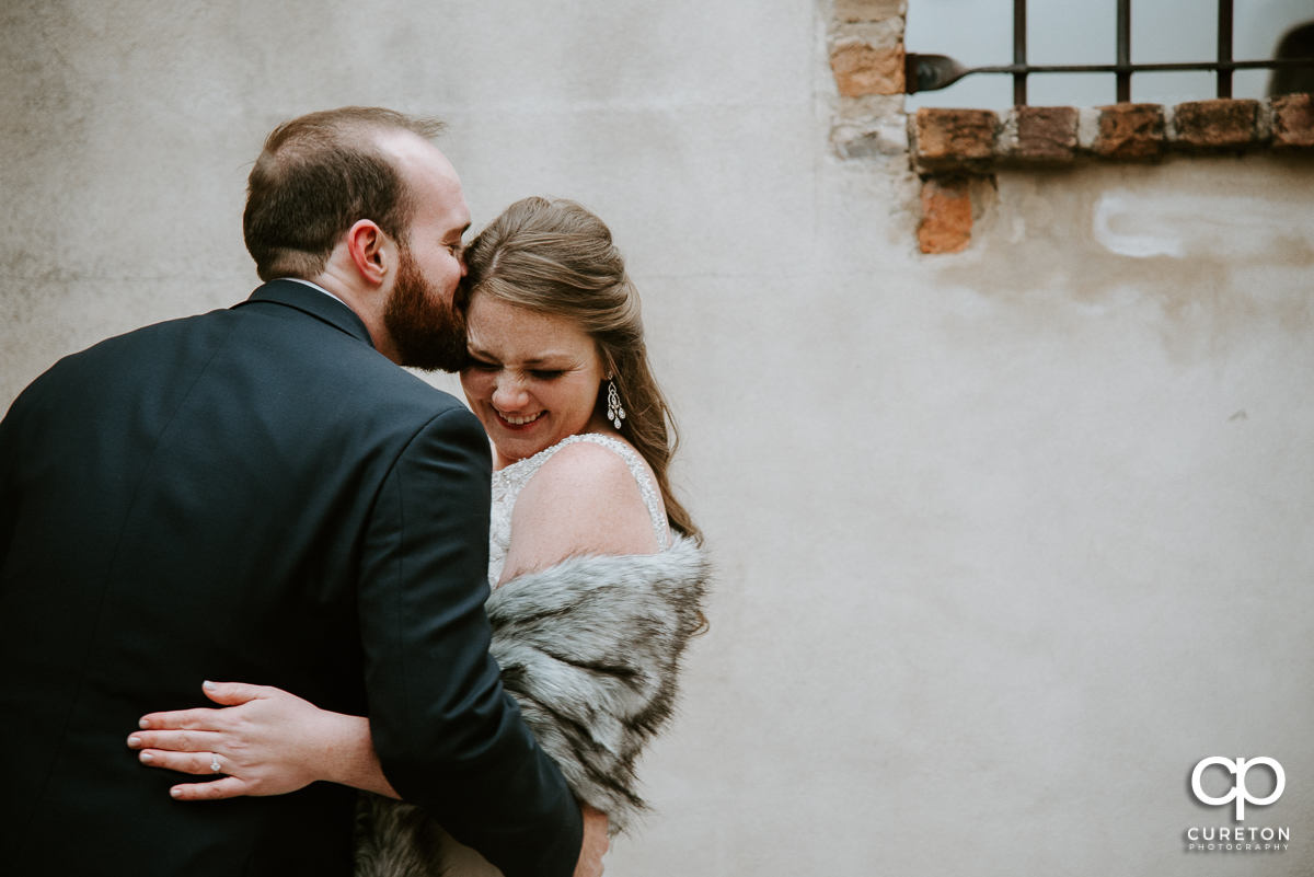 Groom kissing his bride on the forehead as she is laughing.