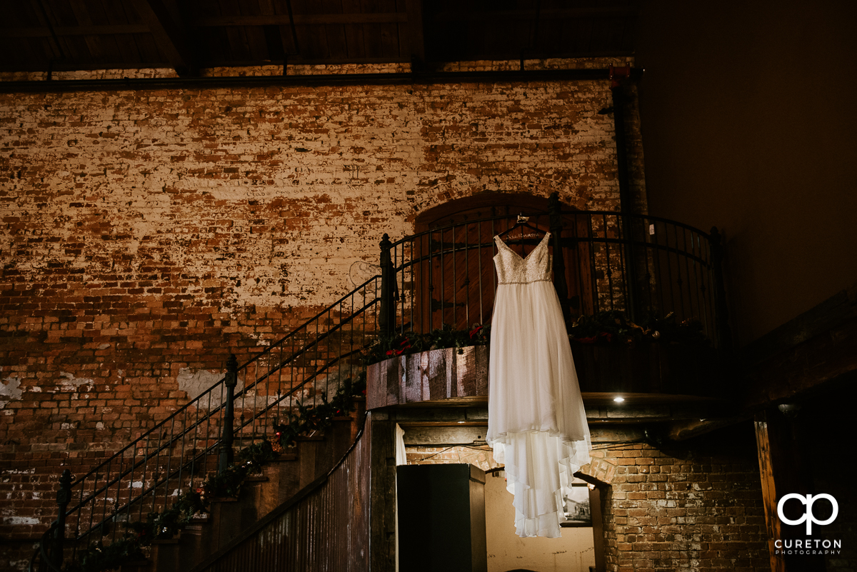 Bride;s dress hanging on the staircase at The Old Cigar Warehouse.