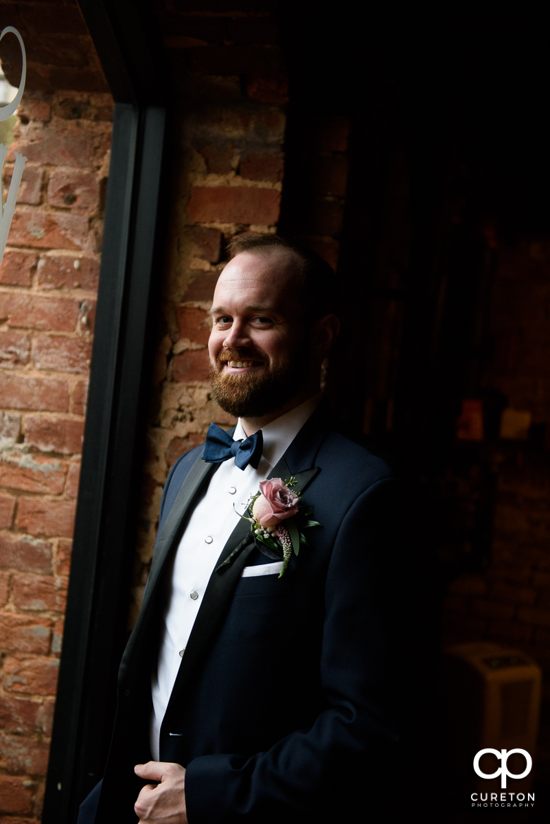Groom smiling in the window before the ceremony.