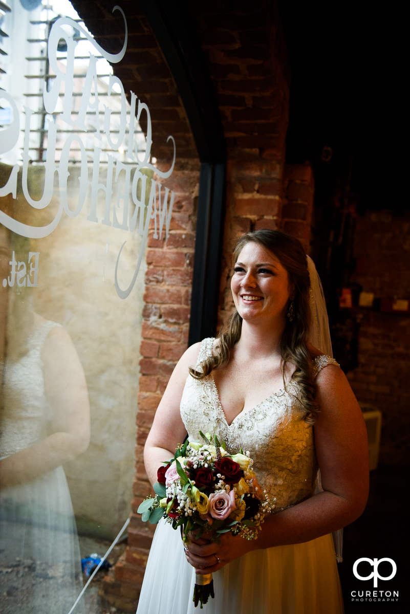 Bride smiling looking out the window.